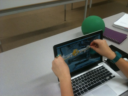 Student using a ruler on a laptop screen.