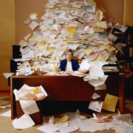 Desk with a huge pile of papers