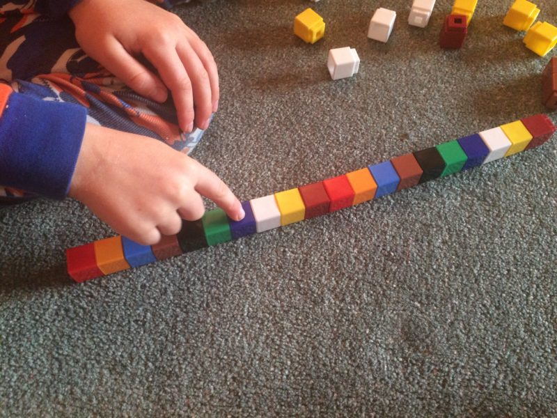A child making a pattern using Unifix cubes.