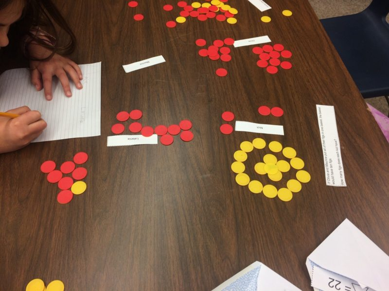 Children using counters to keep track of quantities while working through a word problem.